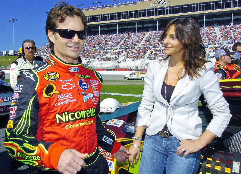 From left, NASCAR driver Jeff Gordan and his wife Ingrid stand at Jeff's car and talk before the start of the Pep Boys 500 Race in Atlanta.