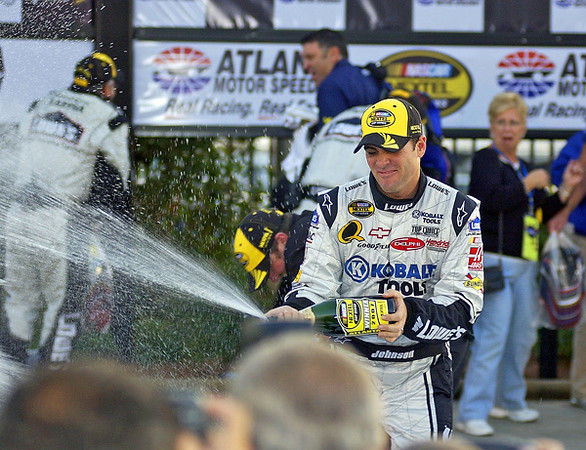 Pep Boys 500 Race Winner Jimmie Johnson sprays the crowd and crew with champagne after his win in Atlanta.
