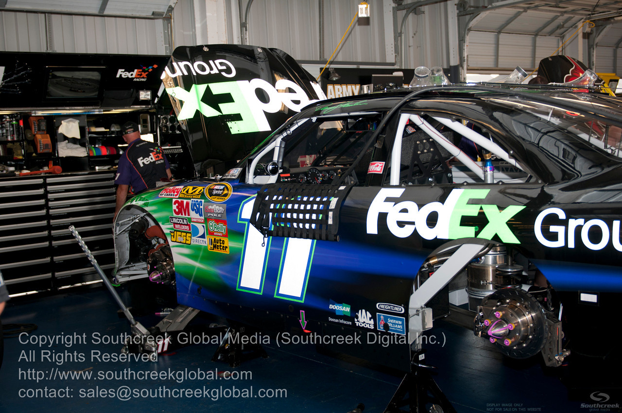 Joe Gibbs Racing crew (11) in the FedEx Ground Toyota garage before the NASCAR Inaugural Quaker State 400 at the Kentucky Speedway Sparta,Kentucky.