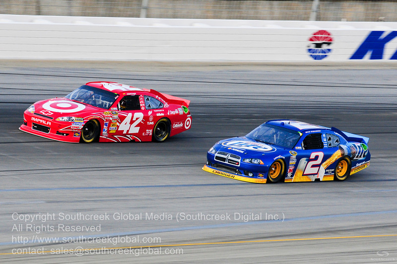 Earnhardt Ganassi Racing driver Juan Montoya (42) in the Target Chevrolet and Penske Racing driver Brad Keselowski (2) in the Miller Lite Dodge during the NASCAR Inaugural Quaker State 400 at the Kentucky Speedway Sparta,Kentucky.