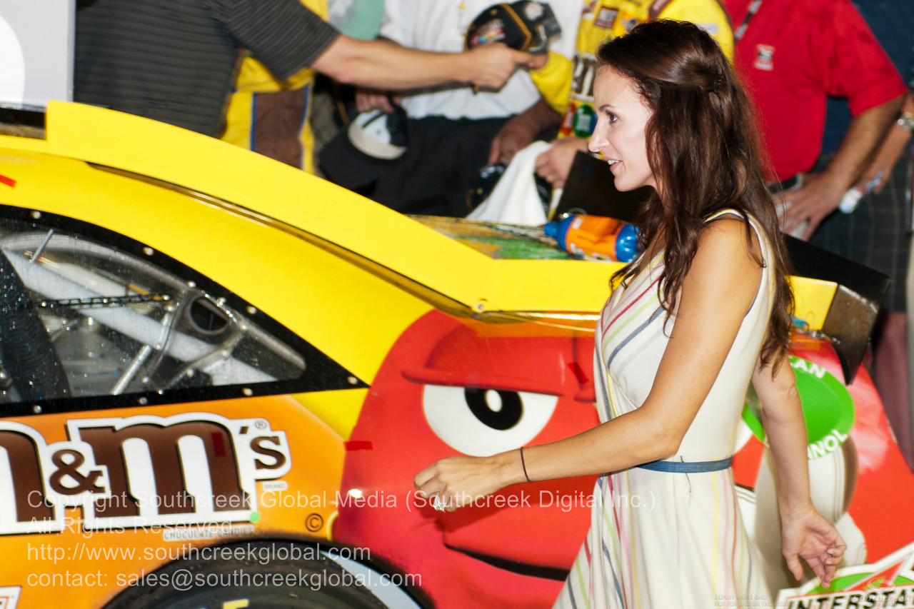 Joe Gibbs Racing driver Kyle Busch (18) in the M&M's Toyota wife after winning the NASCAR Inaugural Quaker State 400 at the Kentucky Speedway Sparta,Kentucky.