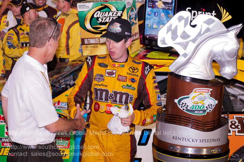 Kentucky Speedway GM Mark Simendinger congratulates Joe Gibbs Racing driver Kyle Busch (18) in the M&M's Toyota after winning the NASCAR Inaugural Quaker State 400 at the Kentucky Speedway  ,Kentucky.