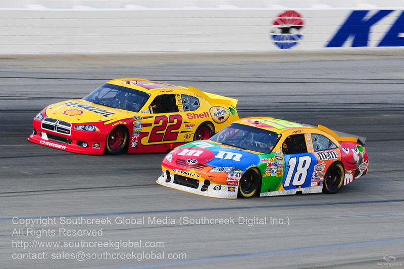 Joe Gibbs Racing driver Kyle Busch (18) in the M&M's Toyota Penske Racing driver Kurt Busch (22) in the Shell/Pennzoil Dodge during the NASCAR Inaugural Quaker State 400 at the Kentucky Speedway Sparta,Kentucky.