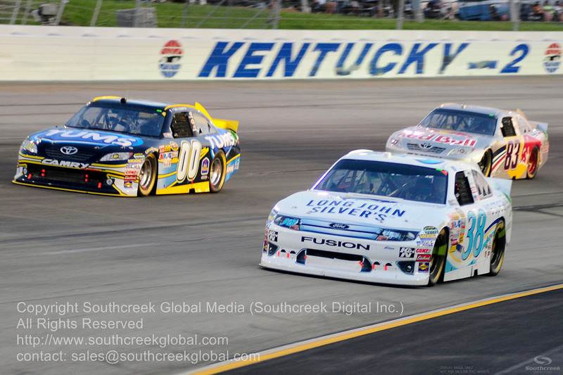 Front Row Motorsports driver Travis Kvapil (38) in the Long John Silver Ford and Michael Waltrip Racing driver David Reutimann (00) in the Tums Toyota with Red Bull Racing Team driver Brian Vickers (83) in the Red Bull Toyota during the NASCAR Inaugural Quaker State 400 at the Kentucky Speedway Sparta,Kentucky.