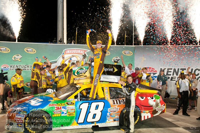 Joe Gibbs Racing driver Kyle Busch (18) in the M&M's Toyota celebrates after winning the Inaugural Quaker State 400.   NASCAR Inaugural Quaker State 400 at the Kentucky Speedway Sparta,Kentucky.
