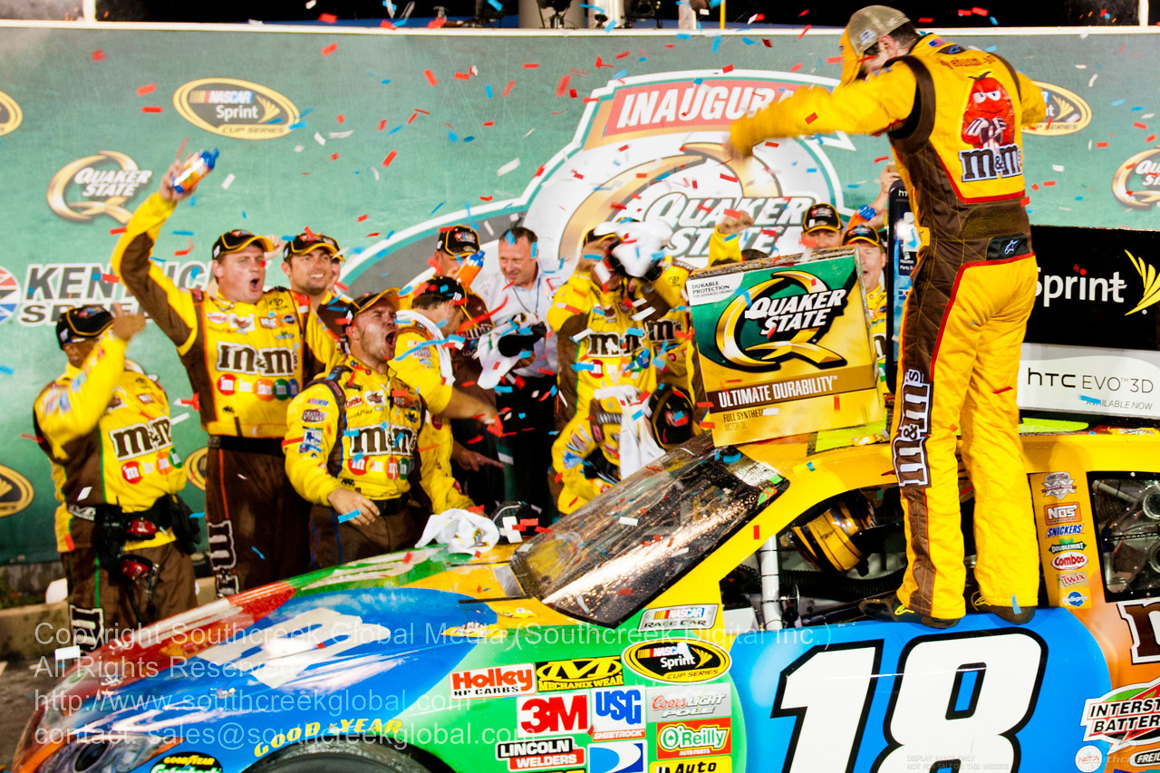 Joe Gibbs Racing driver Kyle Busch (18) in the M&M's Toyota celebrates with his team after winning the  Inaugural Quaker State 400.  NASCAR Inaugural Quaker State 400 at the Kentucky Speedway Sparta,Kentucky.