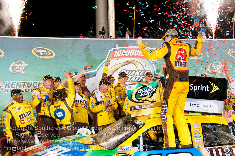 Joe Gibbs Racing driver Kyle Busch (18) in the M&M's Toyota celebrates after winning the  Inaugural Quaker State 400.  NASKAR Inaugural Quaker State 400 at the Kentucky Speedway Sparta,Kentucky.