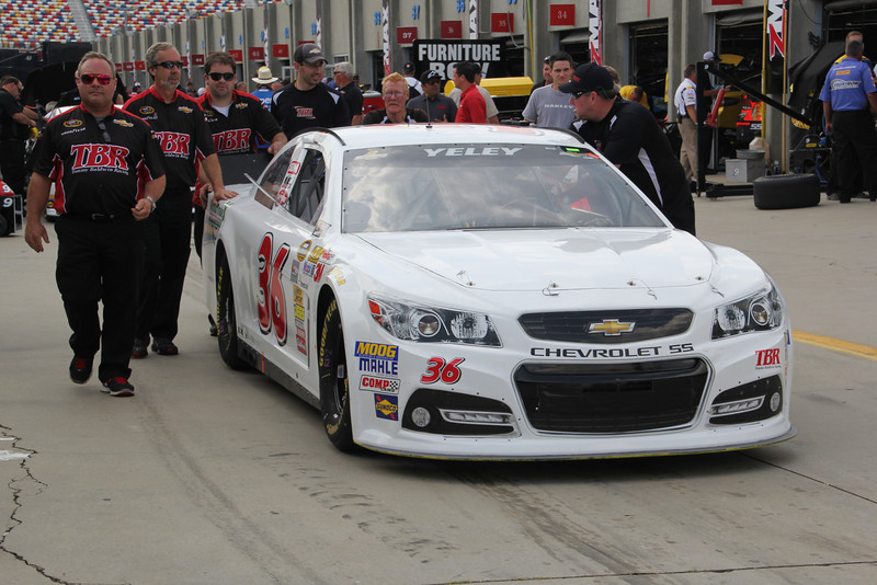 the J J Yeley car is pushed to the NASCAR inspection station.
