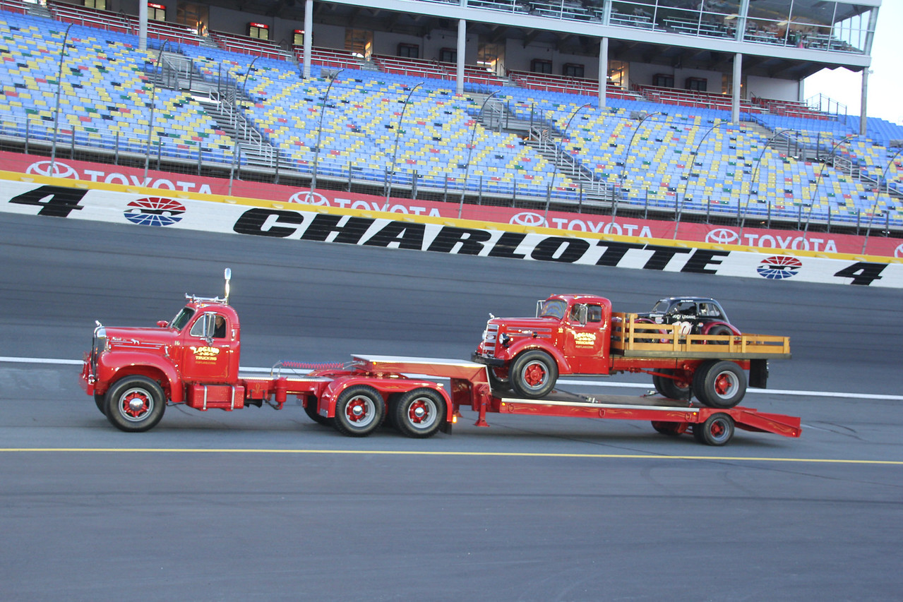 a Logano Trucking carrying a Logano Trucking carrying a Logan race car.