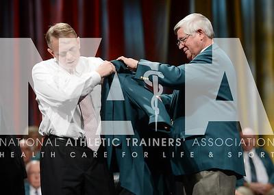 credit: Renée Fernandes Ron Courson, ATC, PT, NREMT-1, puts on his green Hall of Fame jacket during the ceremony.