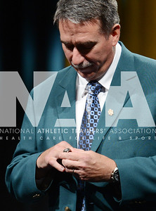 credit: Renée Fernandes Hall of Fame inductee Charlie Thompson, MS, ATC, takes a close look at his ring as he puts it on his finger during the ceremony.