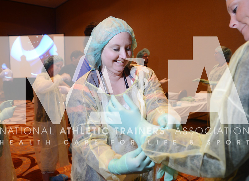 credit: Renée Fernandes Kelsey Findlay, ATC, learns how to put on surgical gloves in a sterile environment during the preconference workshops.