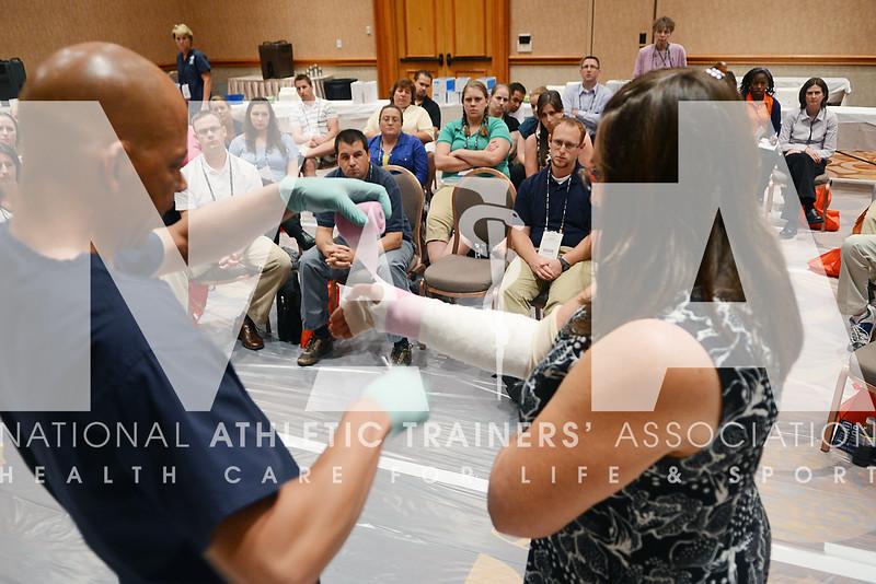 credit: Renée Fernandes Kathleen Cummins, ATC, volunteers to have her arm cast during the preconference workshops.