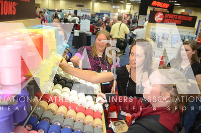 credit: Renée Fernandes Kelley Clonan, ATC, takes a sample from the Cramer booth during the opening day of the trade show.