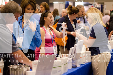 Renee Fernandes/NATA Stacey Ayles, ATC in pink talks with Hartman reps during the AT Expo.
