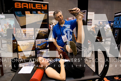 Renee Fernandes/NATA Amy Kunigonis, MS, ATC tries out the Accu-Stretch machine with Vinny Houston at the Baily booth in the AT Expo.