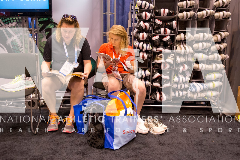 Renee Fernandes/NATA Kathryn Burford, MSE, ATC, left and Sierra Fultz, MA, ATC take a look at a catelog in the Asics booth.