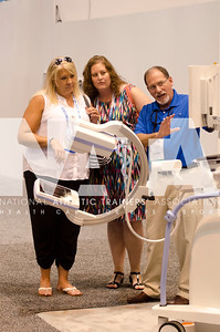 Renee Fernandes/NATA Mary Ann Love, MS, ATC, left and Teah Sonicksen, ATC talks with Richard Keil of Hologic during the AT Expo.