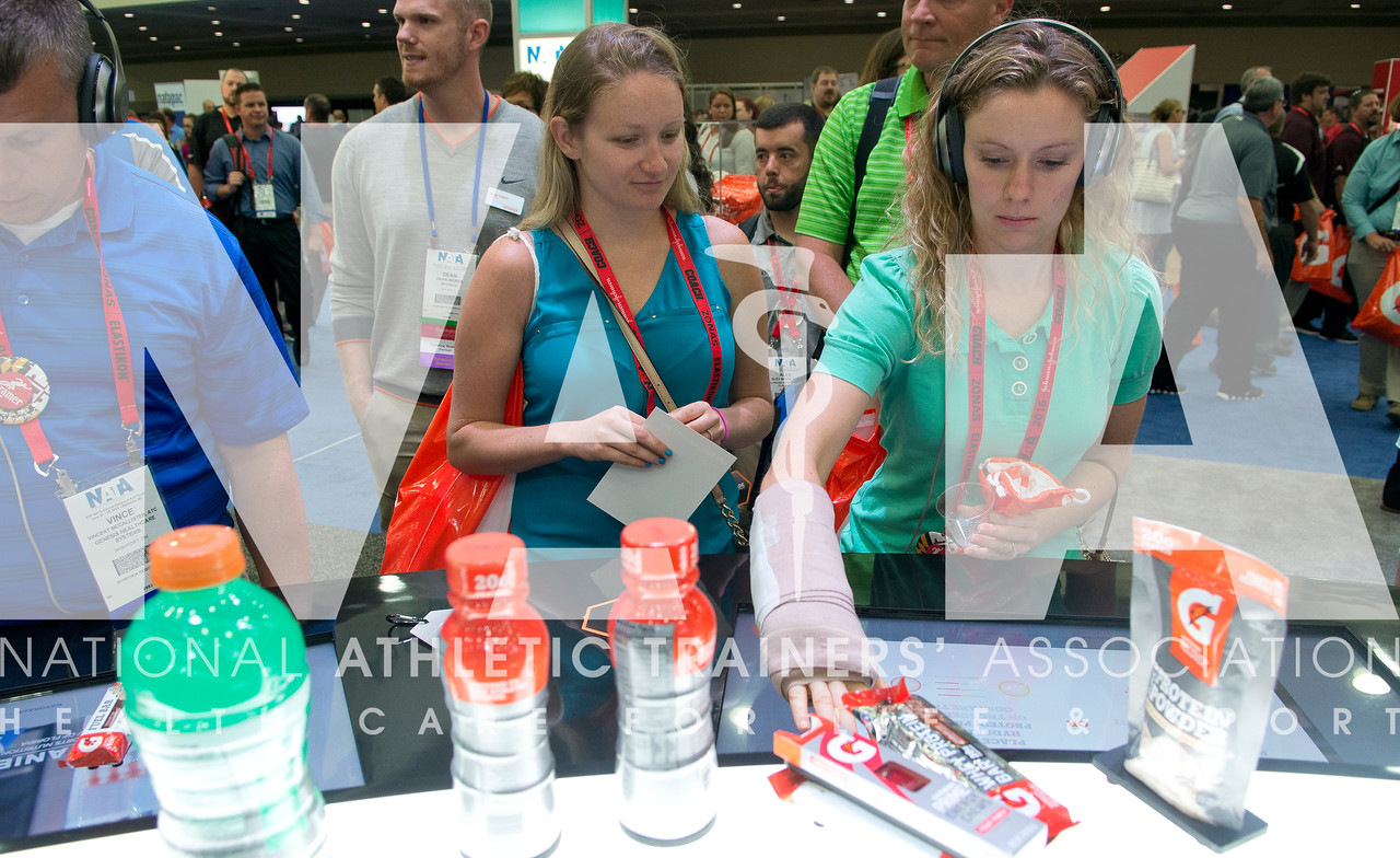 Renee Fernandes/NATA Pamela Bettes, ATC, center and Erin Tufts, ATC, get info abot the products at the Gatorade booth.