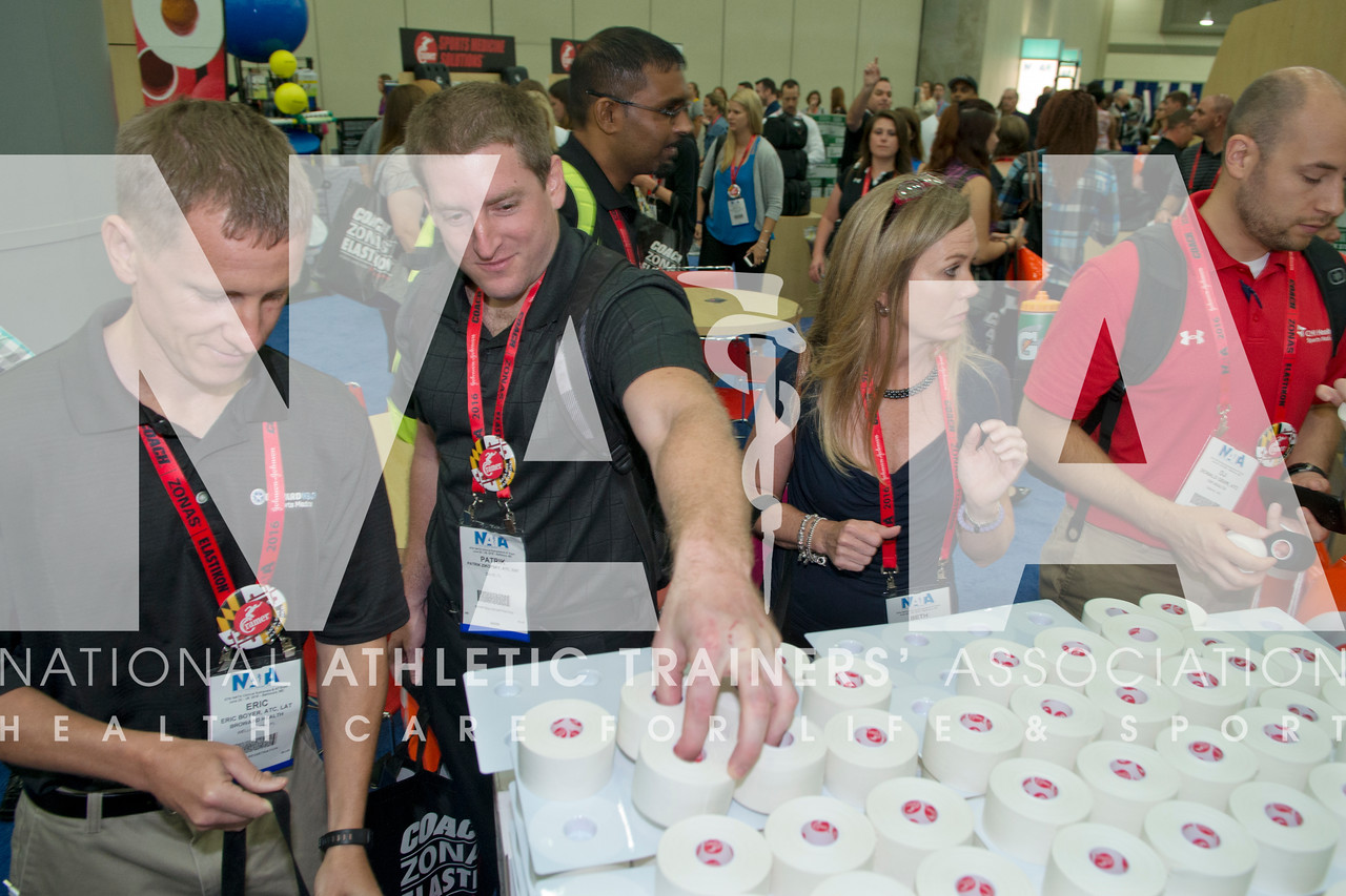 Renee Fernandes/NATA Eric Boyer, ATC, LAT left and Patrick Zikofsky, ATC, EMT grab some samples from the Cramer booth during the first day of the AT Expo.