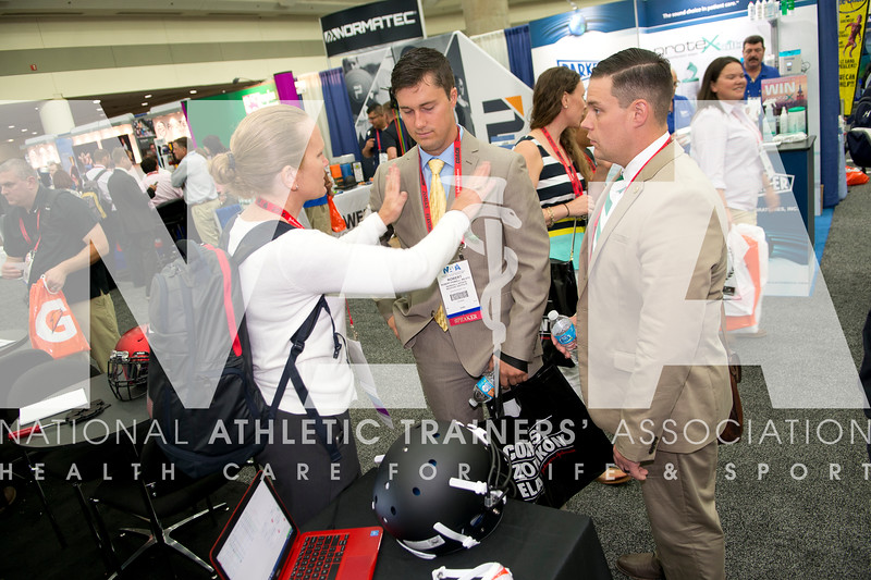 Renee Fernandes/NATA Suzanne Konz, PHD, ATC, CSCS; Robert Powell, MS, ATC and Zach Garrett, MS MHA, ATC talk about products at the Schutt Sports booth at the AT Expo.