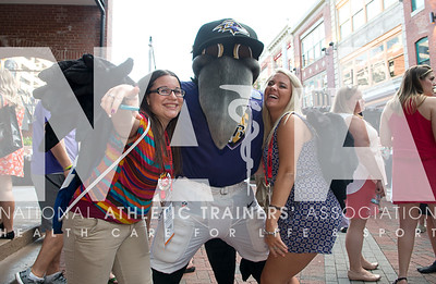 Renee Fernandes/NATA Katelyn Woodward, left and Maggie Smith, have fun with the Baltimore Ravens mascot during the Welcome Reception Wednesday night.