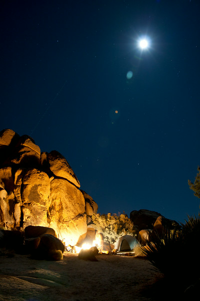 Camp site in Joshua Tree National Park.  Sandstone rock formation lit by a campfire with the full moon shining bright above.