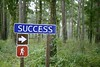 Blue traffic sign with success message in the green forest