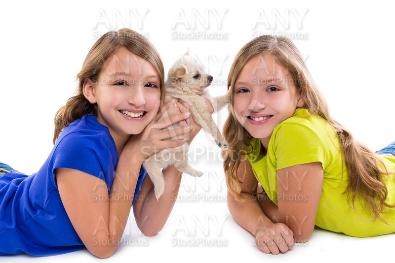 happy twin sister kid girls and puppy dog lying