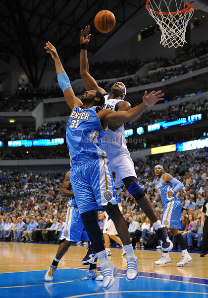 March 29th, 2010  <br /> Dallas Mavericks center Brendan Haywood #33 gets a rebound over Denver Nuggets center Nene Hilario #31<br /> in a game between the Denver Nuggets and the Dallas Mavericks at the American Airlines Center in Dallas, Texas.<br /> Dallas wins 109-93