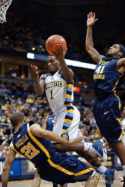 Marquette guard Darius Johnson-Odom (1) is fouled by West Virginia guard Joe Mazzulla (21), while West Virginia forward John Flowers (41) attempts to block the shot, during the game between the Marquette Golden Eagles and the West Virginia Mountaineers at the Bradley Center in Milwaukee, WI. Marquette defeated West Virginia 79-74.   Mandatory Credit: John Rowland / Southcreek Global