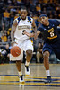Marquette guard Junior Cadougan (5) dribbles past West Virginia forward Kevin Jones (5) during the game between the Marquette Golden Eagles and the West Virginia Mountaineers at the Bradley Center in Milwaukee, WI. Marquette defeated West Virginia 79-74.   Mandatory Credit: John Rowland / Southcreek Global