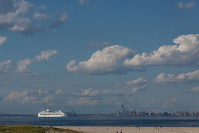 A cruise ship heading out of NY harbor towards the Atlantic.  The tall building near the center of the frame is the new One World Trade in Lower Manhattan seen across Lower New York Harbor/Raritan Bay.  Both of these taken from Sandy Hook, part of Gateway National Recreation Area.  There are many decommissioned former coastal defense batteries here as well as a former Nike Missile base.  No longer active, of course, but they still have missiles, launchers, and mobile control stations that are sometimes open for tours as are some of the batteries.  Sandy Hook is also a major flyway for migratory birds and monarch butterflies.  A very unique & beautiful natural place in sight of it's exact opposite.