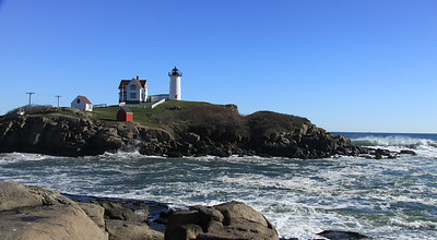 This is the Nubble Lighthouse at Cape Neddick, ME.  It's on a small island maybe 100 yards off the coast.  No public access, but staff access is via a little car that traverses a cable and pulley over to the light...see the poles & small white car on the left of photo.  How'd you like to be in that in a winter storm?