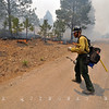 A wildland firefighter works a backblaze in the Escudilla Mountain Wilderness intended to slow the Wall Fire which burns only a few hundred feet away. -Apache County, AZ