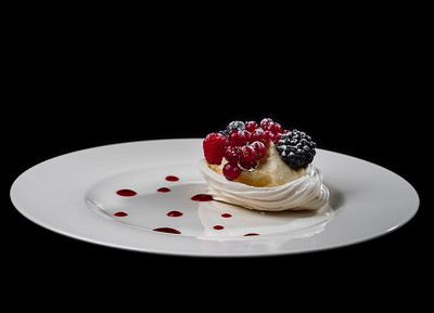 Delicious cake with berries: red currants, blueberries, blackberries. Cream and beautiful shape. Dessert in the restaurant.