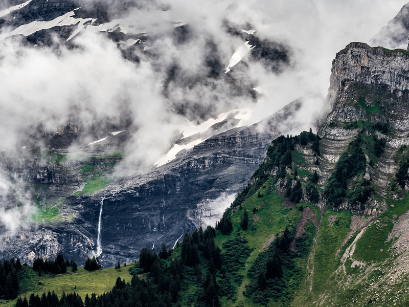 Stunning cliffs high in the Swiss Alps. Clouds, snow on the peaks and waterfalls.