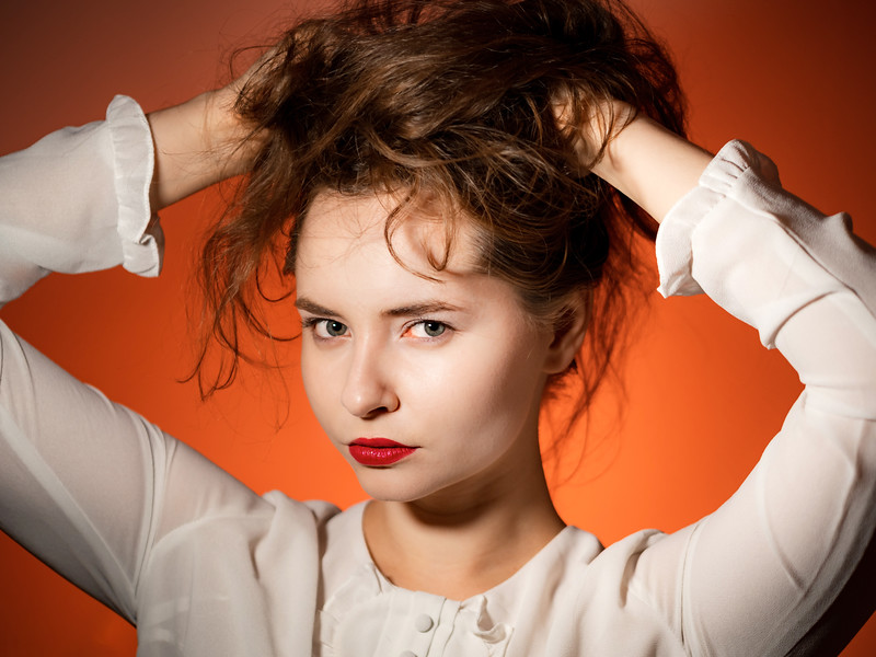Beautiful young girl posing with her hair down on an orange background. Energy and youth. Attractiveness and sexuality.