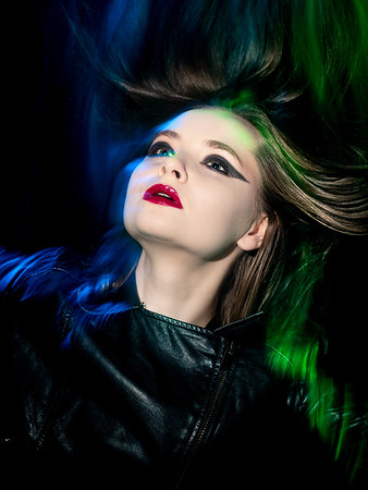 Expressive studio portrait of a beautiful young girl. The movement of the hair is accentuated by vibrant colors on the sides.