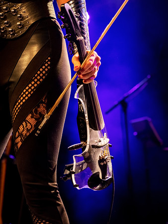 Electric violin in the hands of a beautiful woman musician, rock concert