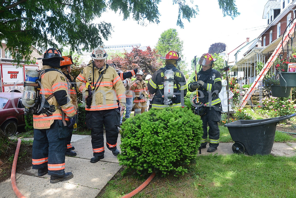 . Fire fighters on stand-by in the front yard of a house fire on E 8th Street.  Friday, May 30, 2014.  Photo by Adrianna Hoff/Times Herald Staff.