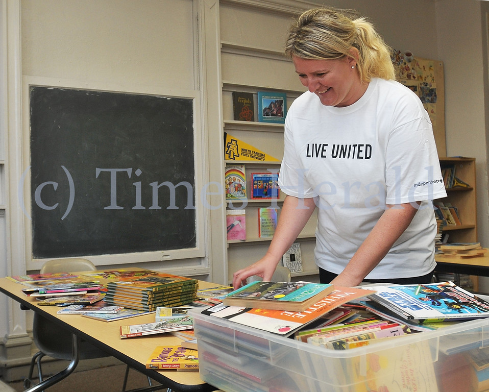 . Anna Plotka organizes picture and chapter books into piles for elementary school age, middle school age, and high school age students.  Monday, September 30, 2013.  Photo by Adrianna Hoff/Times Herald Staff.