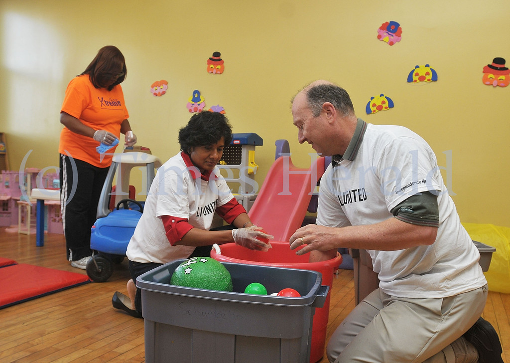 . While Shyla Jagannatha and Rob Labadie clean off plastic balls, Denise Ashe works on cleaning different toys behind them.  Monday, September 30, 2013.  Photo by Adrianna Hoff/Times Herald Staff.