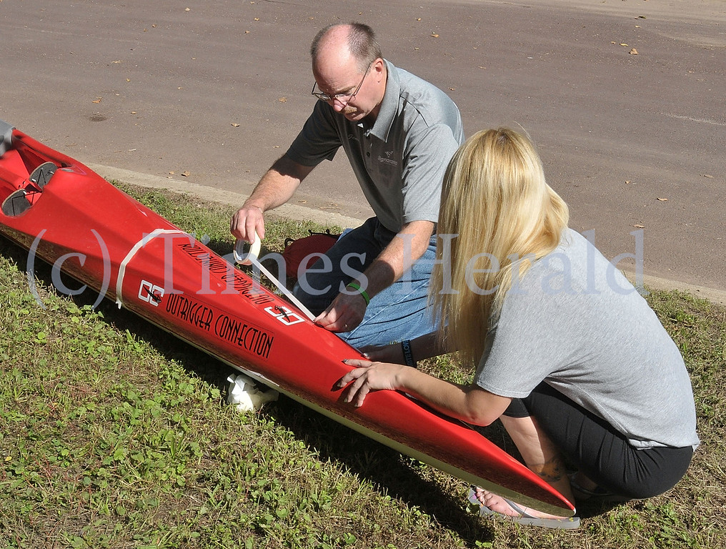 """. Gene Schneider and Annie Damico from Signarama helped add the new \""""Riverfront Rangers\"""" logo to the Outrigger Canoe.  The Canoe was dedicated to the Norristown community members who have helped the Dragon Boat Club to fix up and maintain Riverfront Park.  Saturday, September 21, 2013.  Photo by Adrianna Hoff/Times Herald Staff."""