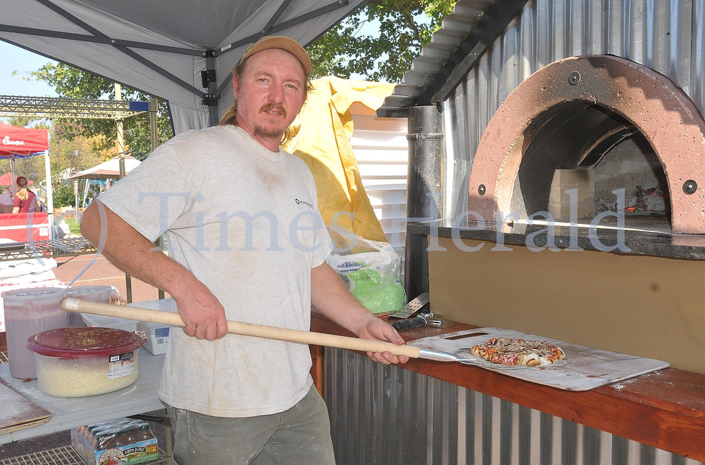 . Sean Wylde from Wylde Fire Trading Company of Boyertown pulls out a fresh wood fired pizza from his oven at the Lower Providence Fall Fest.  Saturday, October 5, 2013.  Photo by Adrianna Hoff/Times Herald Staff.