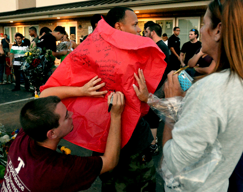 . Marquis Allen uses the back of Cesar Nuesi to sign a heart-shaped paper hot air balloon, one of many filled and released later Monday evening, Aug. 25, 2014 in memory of the victim of a fatal accident along Broad St., Hatfield. At right is Kelly Haynes, mother of one of the victim\'s friends. Montgomery Media staff photo by Bob Raines