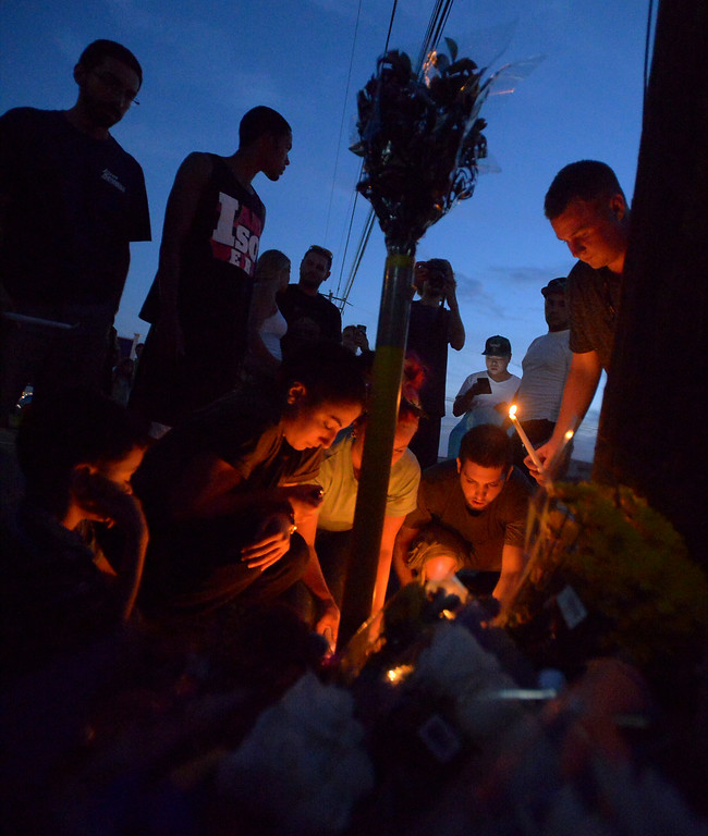 . Mourners light candles at a roadside shrine marking the site of a recent fatal crash along Broad St., Lansdale Monday night, Aug. 25, 2014  Montgomery Media staff photo by Bob Raines