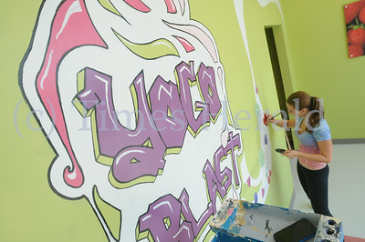 Local artist Emily Dupont paints a mural on the walls of Yogo Blast store in Oaks