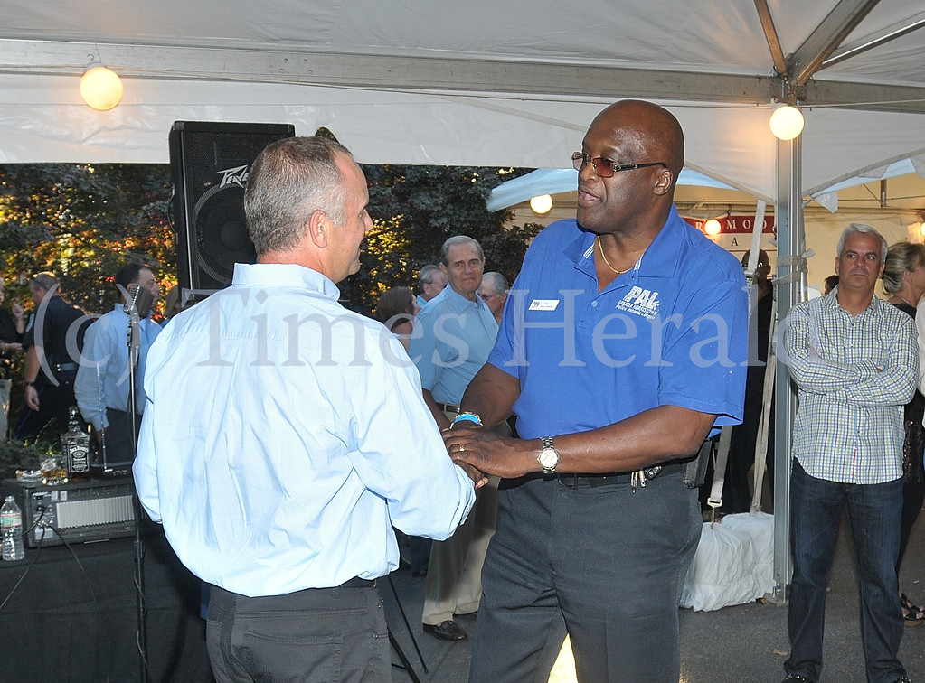 . Norristown Police Chief Willie G. Richet congratulates Michael Fink on his Community Service Award from the Greater Norristown Police Athletic League.  Thursday, September 5, 2013.  Photo by Adrianna Hoff/Times Herald Staff.