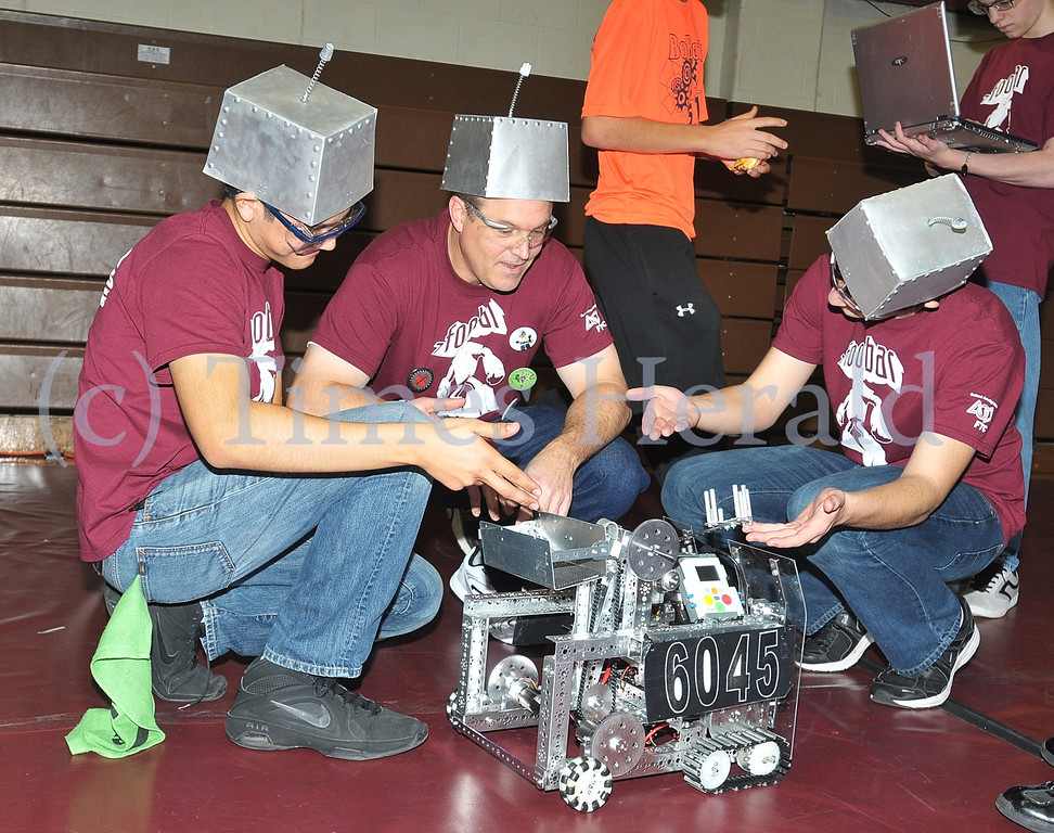 . Ariosto Gomez, Brian Hildebrandt, and Nick Russell from team Foobar of Oxford, PA, look over their robot before the competition at Montgomery County Community College Physical Education Building.  Saturday, December 7, 2013.